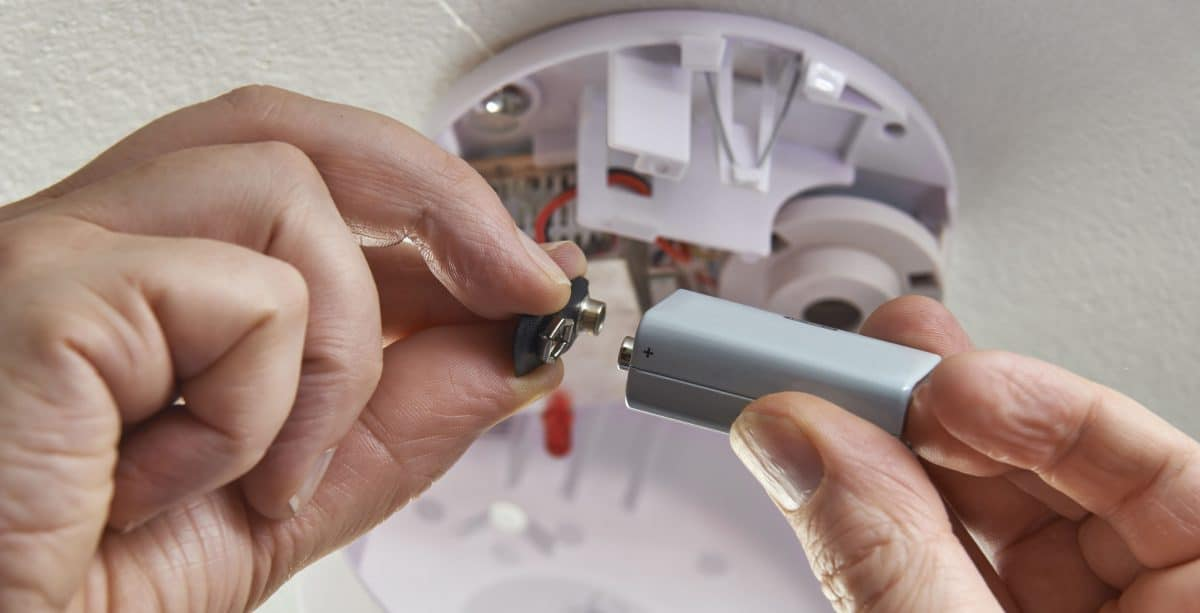 Person changing battery in smoke detector
