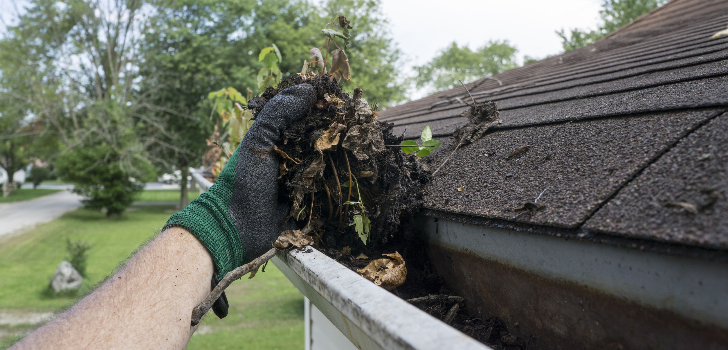 Hands Cleaning Gutters Filled With Leaves and Sticks