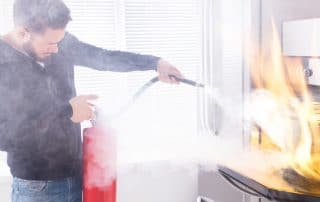 Man using extinguisher to put out oven fire