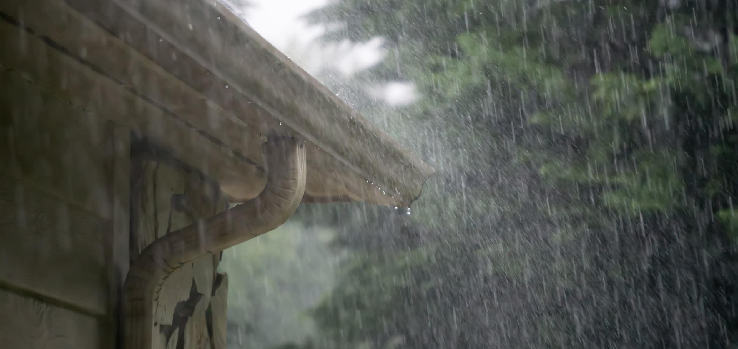 Heavy rain pouring onto home roof and gutter
